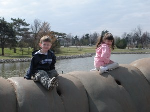 The kids sitting on the giant caterpillar outside